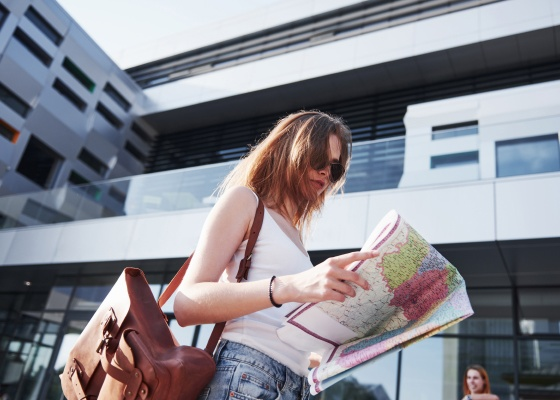 Female tourist with map visiting a new city and is looking for a way to the hotel.